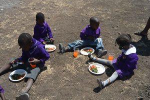 Skolbarnen äter sin lunch på marken